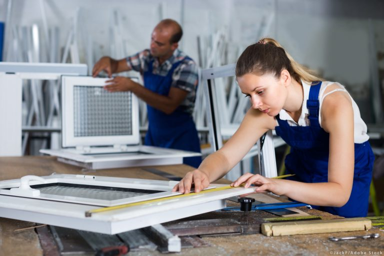 Craftswoman is checking dimensions of finished plastic window us